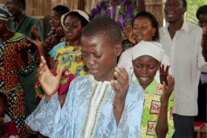 young boy worships in rural Benin (West Africa)
