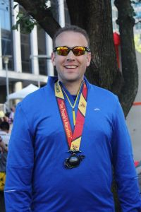 Chris shows off his medal received for finishing the Marine Corps marathon, October 2014