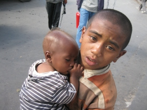 A street boy carries an infant while begging from motorists in the streets of Antanananarivo.